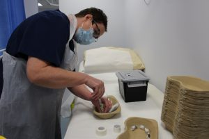 Nurse carefully preparing a Pfizer vial